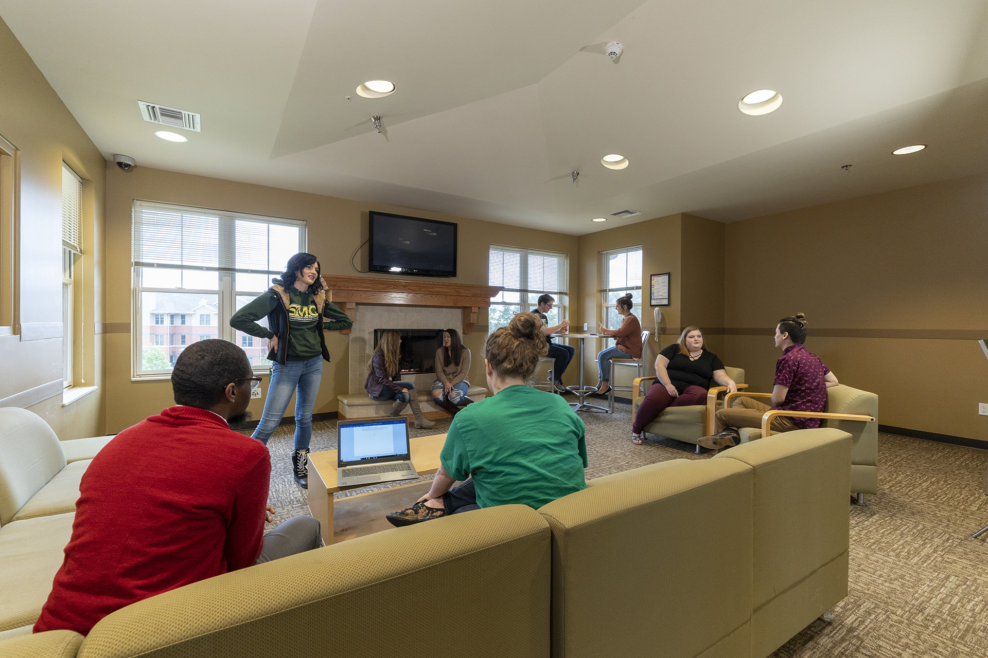 Students talking and watching TV in the Residence Halls common area
