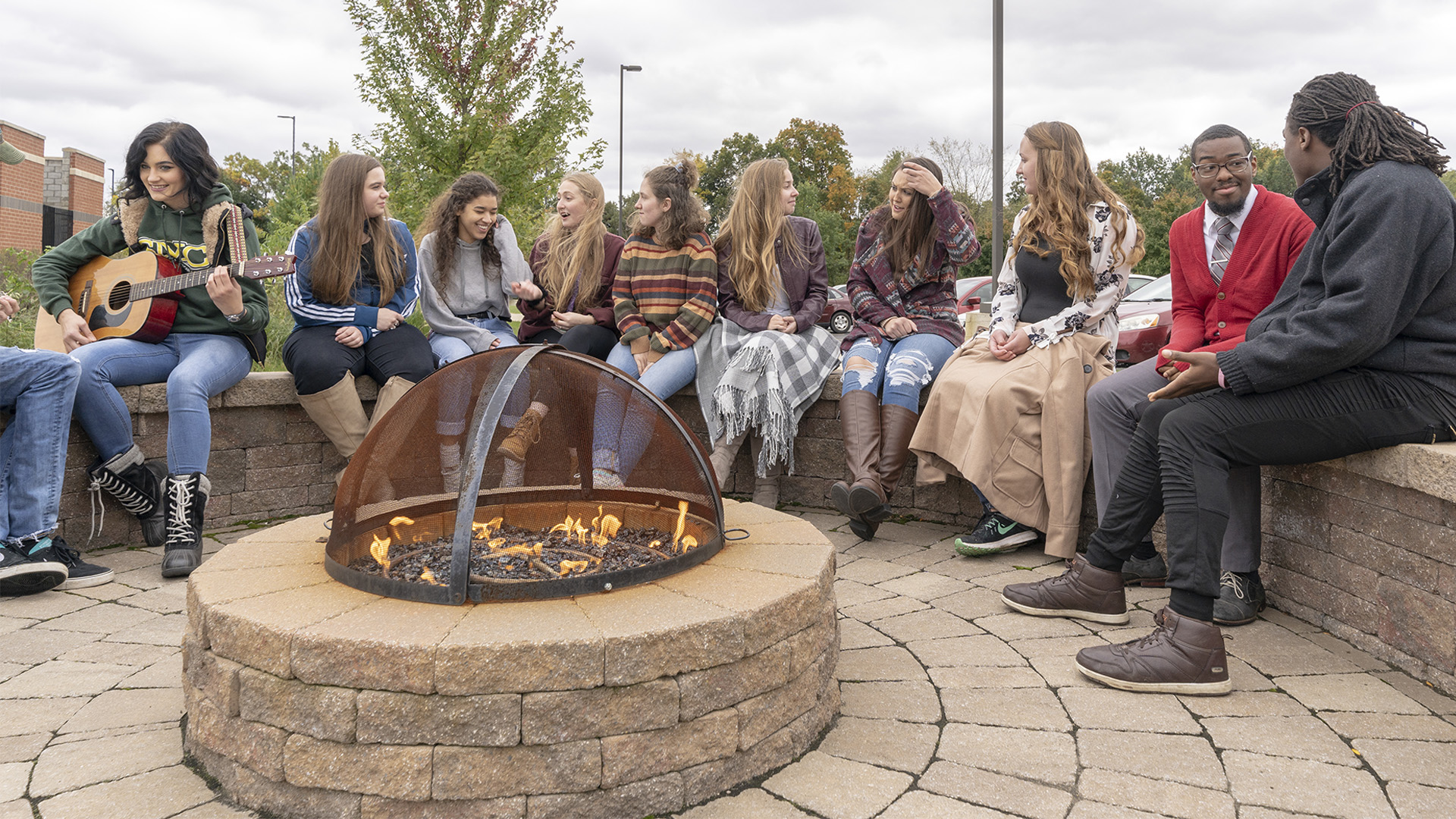 Students sitting around the residence halls firepit